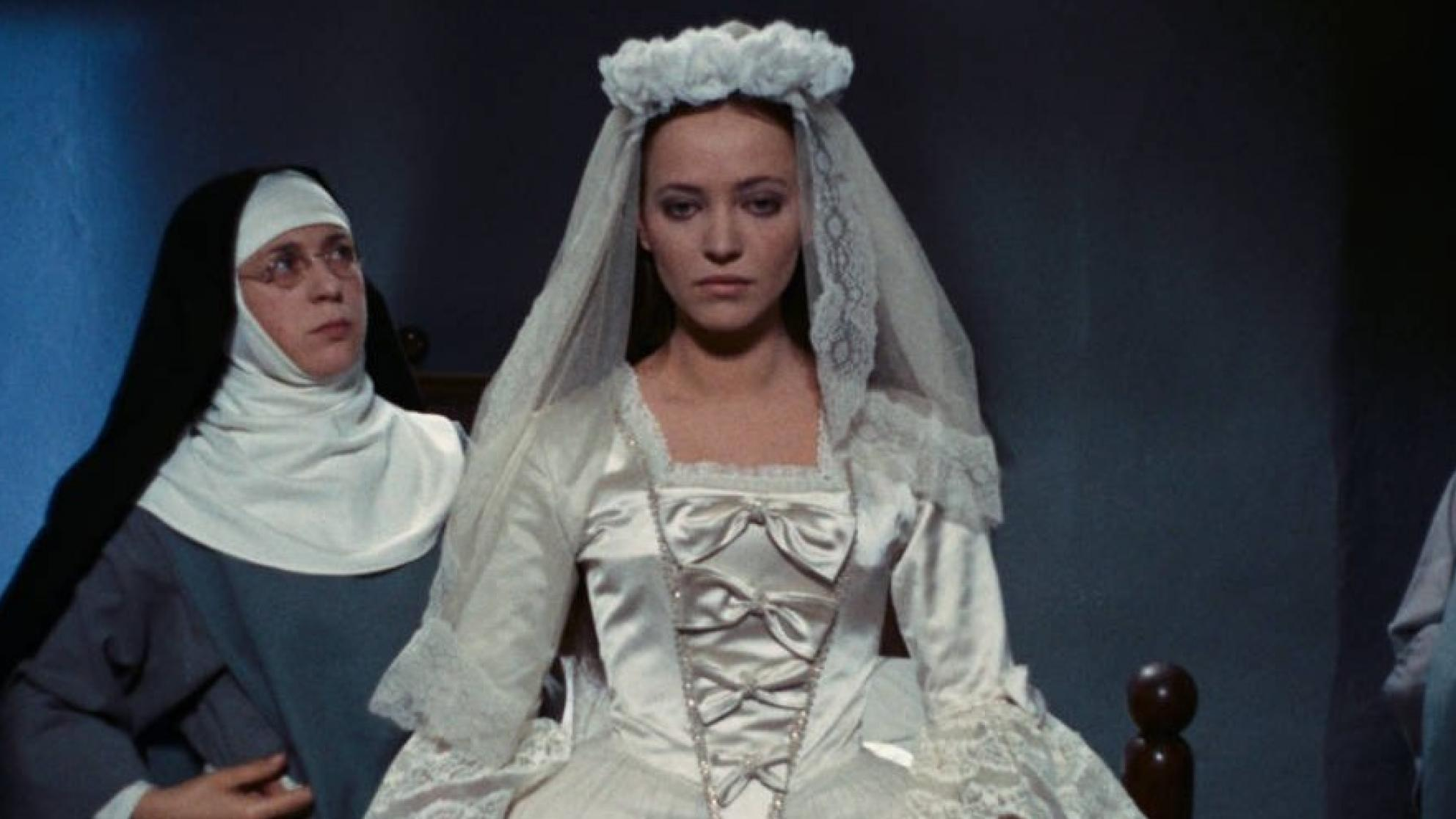 A young woman in a wedding gown stands centre of frame while a nun to her right looks at her intensely