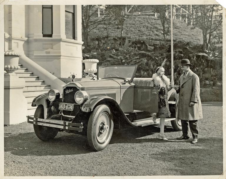 A 1926 motor vehicle parked outside a mansion, a man and woman stand beside the car.