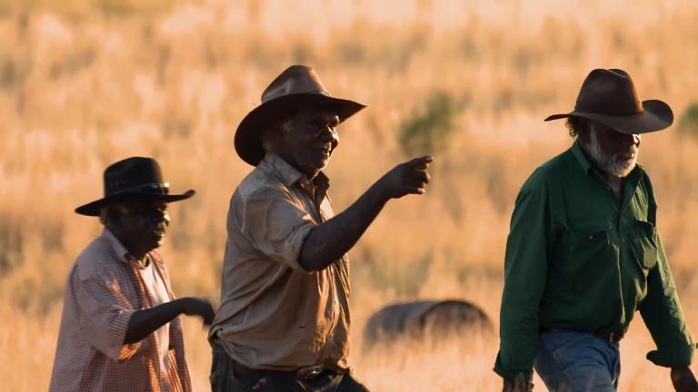 Three Aboriginal men walking in the outback