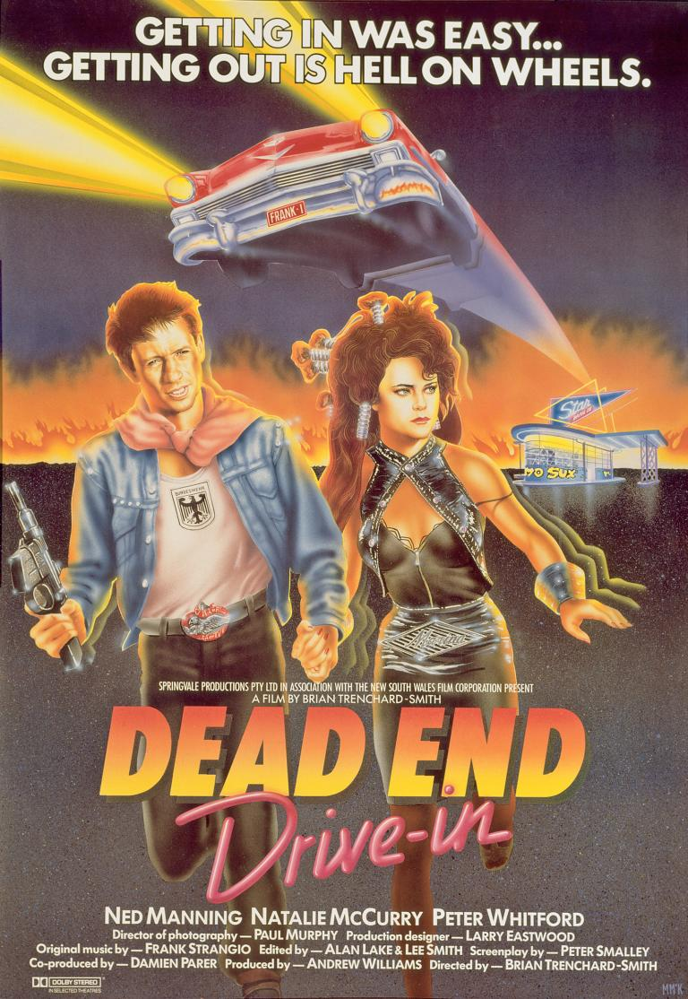 Poster art for the film Dead End Drive-In show a young man holding a machine gun and woman running away from a drive-in cinema. There is a red car with headlights on hovering above their heads. The film title and credits are at the bottom.