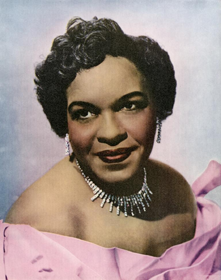 Coloured studio portrait of Winifred Atwell wearing a pink off the shoulder dress, ear rings and necklace
