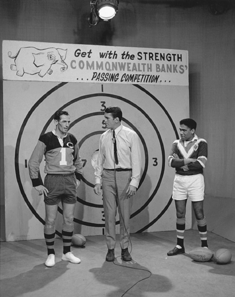 Black and white photo on set of The Rugby League Show with Rex Mossop centre, Ken Irvine to his right and Bruce Stewart on his left in front of the pass the ball competition taget.