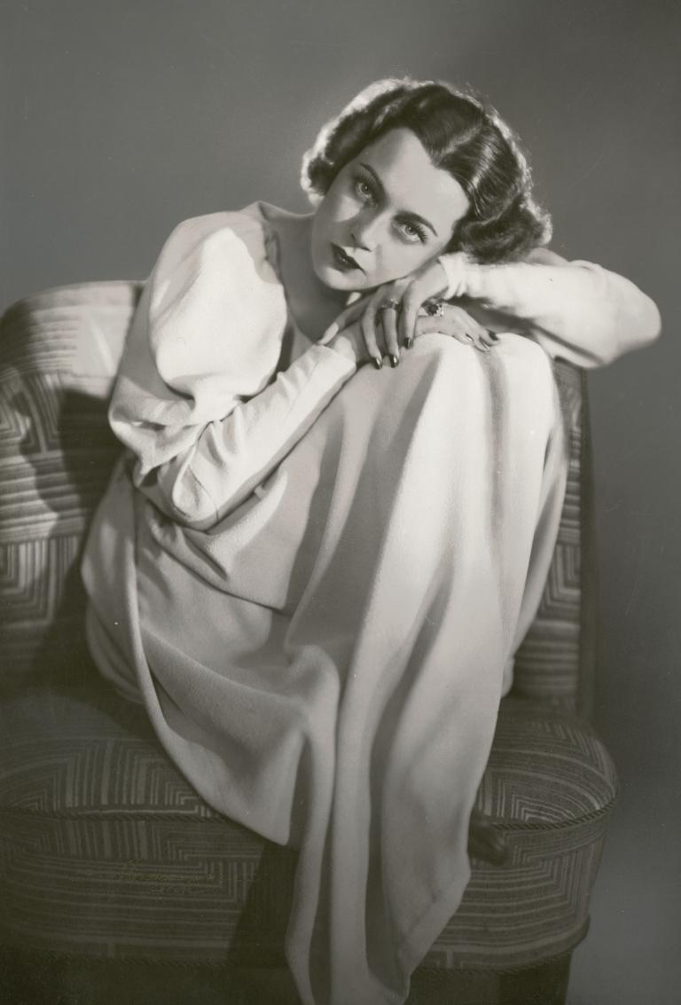 Portrait of Baroness Luli von Hohenberg who is seated and resting her head on her hands.