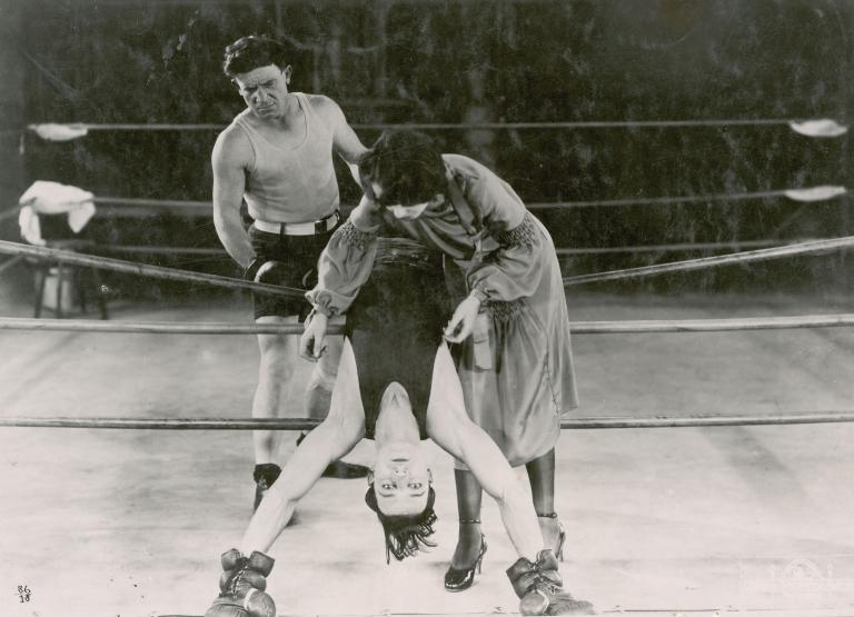 Buster Keaton leans backwards over the ropes in a boxing ring in a still from Battling Butler, 1926.