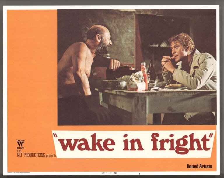 Wake in Fright film lobby card featuring a photo of Donald Pleasence and Gary Bond seated at a table in Doc's outback hut