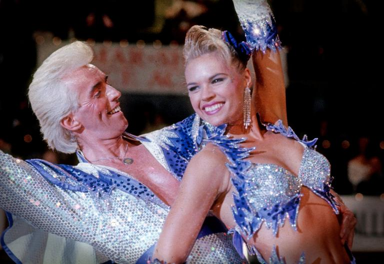 Scene from Strictly Ballroom showing Ken Railings (John Hannan) and Tina Sparkle (Sonia Kruger) in a dance pose wearing matching sequinned outfits.