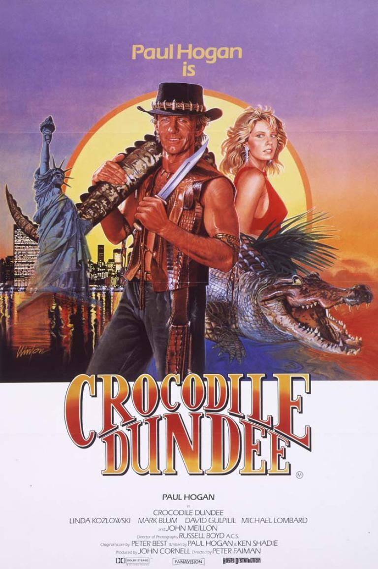 Australian poster for Crocodile Dundee showing illustrations of Mick Dundee, Sue Charlton and a crocodile with the outback and the New York City skyline as backgrounds