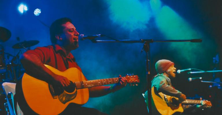 Musician Dave Adern with Archie Roach on stage singing.