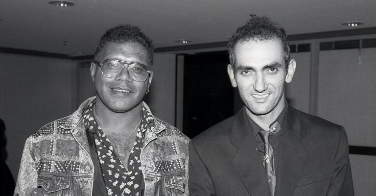 A black and white photograph of Archie Roach and Paul Kelly. Archie holds an ARIA award in his hand. They are both smiling.