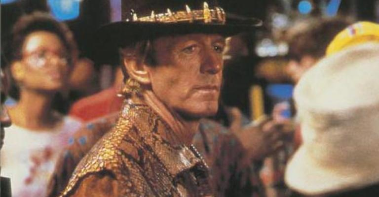 Lobby card depicting Paul Hogan as Mick Dundee standing in a bar in New York City by himself