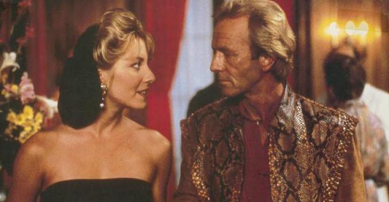 Lobby card depicting Linda Kozlowski as Sue Charlton and Paul Hogan as Mick Dundee looking into each other's eyes