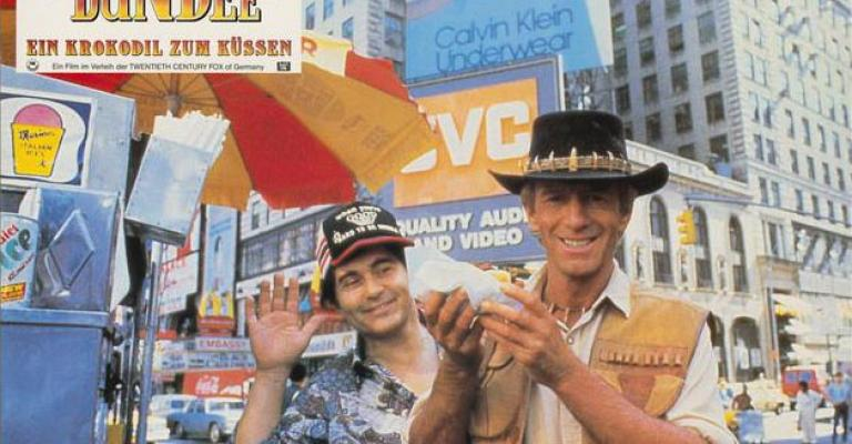 Lobby card depicting Paul Hogan as Mick Dundee holding a hot dog and smiling for the camera in New York City